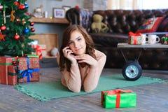 微笑的女孩在地板上说谎在格子花呢披肩作梦和,摆在为pho 免版税库存图片