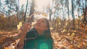 微笑的女孩在坐在晴朗的秋天森林里的干燥事假看 影视素材