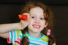微笑的女孩在手上拿着一个草莓在巧克力背景 免版税库存照片