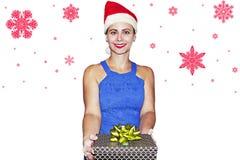 微笑的女孩在有礼物盒的圣诞老人帽子在手中在与红色雪花的白色背景 库存图片