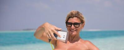 微笑的女孩在海滩做selfie 库存图片