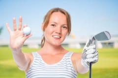 微笑的女孩在球和高尔夫俱乐部显示一台照相机 免版税库存照片