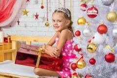 微笑的女孩坐与一件巨大的礼物的一条长凳从圣诞树 图库摄影