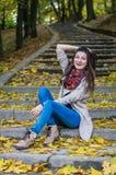 微笑的女孩坐台阶 免版税库存照片