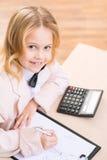 微笑的女孩坐在书桌和画 免版税库存图片