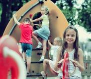 微笑的女孩坐在儿童的游乐场的摇摆 库存照片