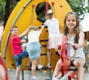 微笑的女孩坐在儿童的游乐场的摇摆 库存图片