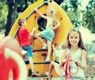 微笑的女孩坐在儿童的游乐场的摇摆 免版税库存图片