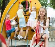 微笑的女孩坐在儿童` s操场的摇摆 图库摄影
