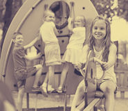 微笑的女孩坐在儿童` s操场的摇摆 库存照片