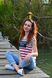 微笑的女孩坐在河上的桥梁 库存图片