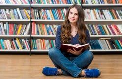 微笑的女孩坐地板在有阴级射线示波器的图书馆里 免版税库存图片