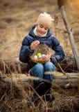 微笑的女孩坐树日志在有复活节篮子的森林 免版税库存图片