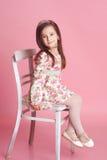 微笑的女孩坐椅子在屋子里 免版税库存图片