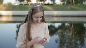 微笑的女孩坐河的散步 股票录像