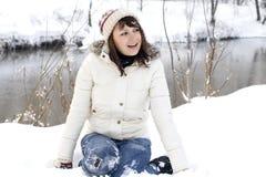 微笑的女孩坐随风飘飞的雪 免版税库存图片