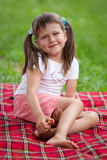 微笑的女孩学龄前儿童坐格子花呢披肩在公园 免版税库存照片