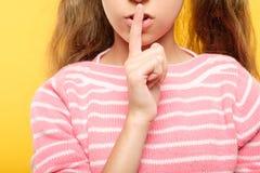 微笑的女孩手指嘴唇淘气秘密阴谋 免版税库存照片