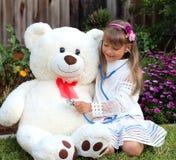 微笑的女孩扮演有巨大的玩具白熊的医生 免版税库存图片