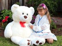微笑的女孩扮演有巨大的玩具白熊的医生 免版税库存照片