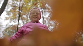 微笑的女孩投掷的槭树叶子在秋天 股票录像