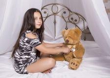 微笑的女孩拥抱一个玩具熊,在家坐她的床 免版税库存图片