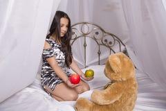 微笑的女孩拥抱一个玩具熊,在家坐她的床 免版税图库摄影