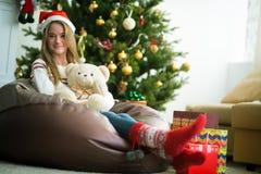 微笑的女孩拥抱在圣诞前夕的玩具熊 库存照片