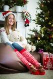 微笑的女孩拥抱在圣诞前夕的玩具熊 库存图片