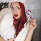 微笑的女孩拿着红色圣诞节玩具 在白色毛皮的美好的妇女模型 免版税图库摄影