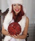 微笑的女孩拿着红色圣诞节球 在白色毛皮的美好的妇女模型 库存图片