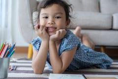 微笑的女孩拿着铅笔和,这一亚裔女孩在家充当客厅 她非常愉快地微笑 免版税库存照片