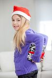 微笑的女孩掩藏的圣诞节礼物后边后面 库存图片
