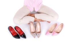 微笑的女孩提出在白色背景隔绝的三个现代对高跟鞋 库存图片