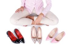 微笑的女孩提出在白色背景隔绝的三个现代对高跟鞋 免版税库存照片