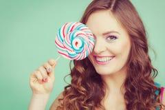 微笑的女孩用在小野鸭的棒棒糖糖果 库存图片