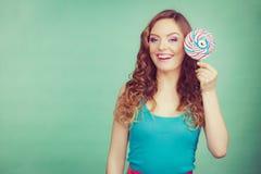 微笑的女孩用在小野鸭的棒棒糖糖果 免版税库存图片
