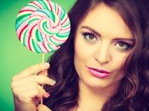 微笑的女孩用在绿色的棒棒糖糖果 图库摄影