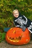 微笑的女孩用巨大的万圣夜南瓜杰克O'Lantern 图库摄影