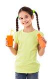 微笑的女孩用红萝卜和杯汁液 免版税图库摄影