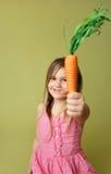 微笑的女孩用红萝卜 图库摄影