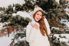 微笑的女孩画象摆在树旁边的温暖的白色外套的在冷淡的天 浪漫夫人室外照片有长期的 免版税库存图片