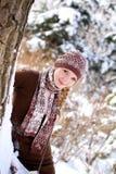微笑的女孩纵向在结构树附近的在冬天公园 免版税库存照片