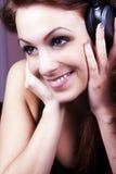 微笑的女孩耳机听的音乐 免版税库存照片
