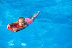 微笑的女孩获得与浮动委员会的乐趣在游泳池 免版税库存照片
