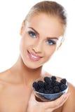 微笑的女孩藏品黑莓在手边 库存照片