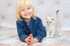 微笑的女孩躺下和 英国品种的小猫是步行 库存图片