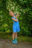 微笑的女孩近的开花的茉莉花 免版税图库摄影