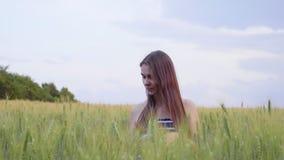 微笑的女孩通过麦田走在日落 股票视频