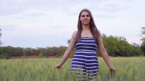 微笑的女孩通过麦田走在日落 股票录像